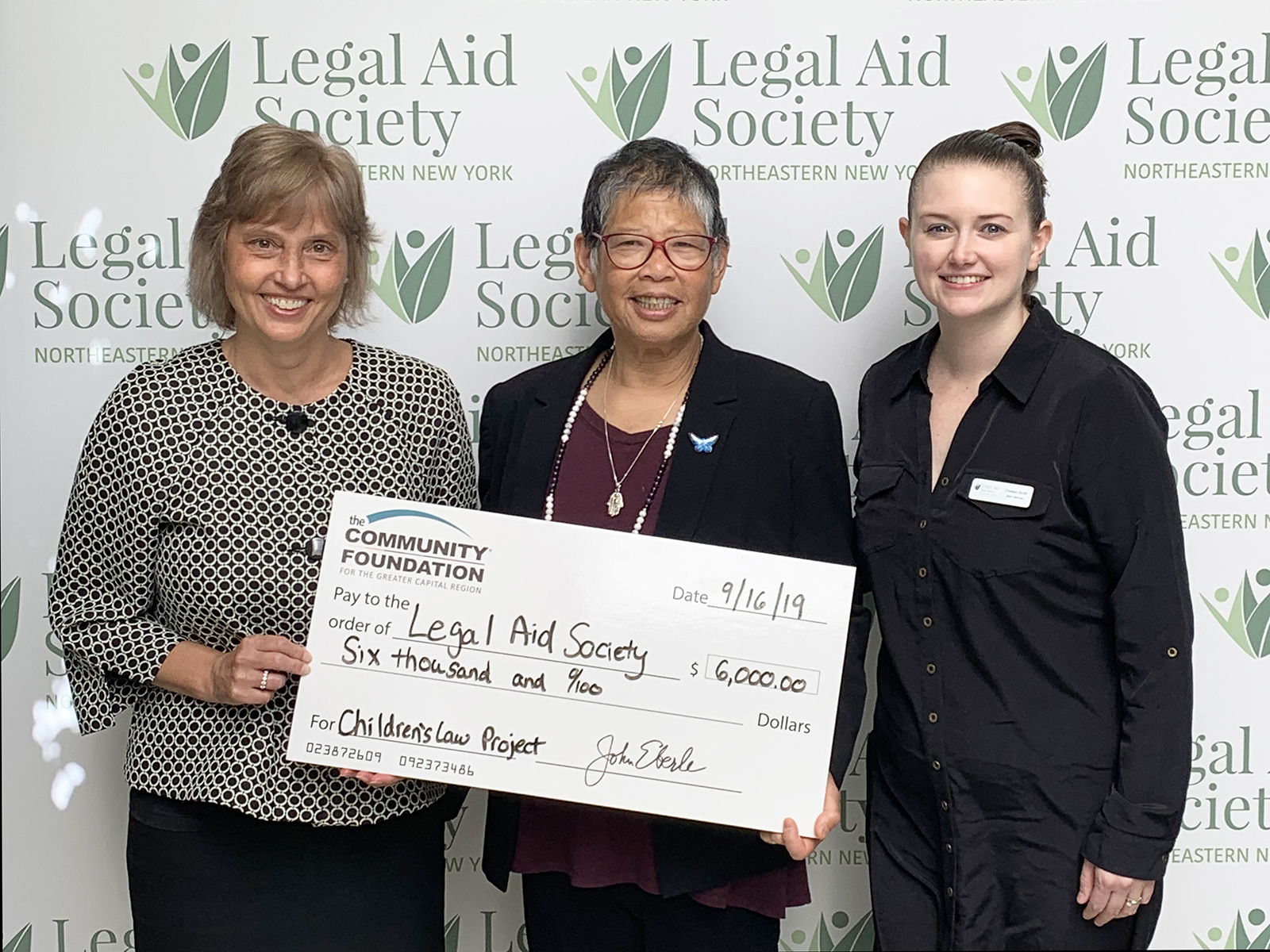Community Foundation Vice President of Community Grantmaking, Shelly Connolly presents the grant check to LASNNY Executive Director Lillian M. Moy and LASNNY CLP Attorney Christen Smith
